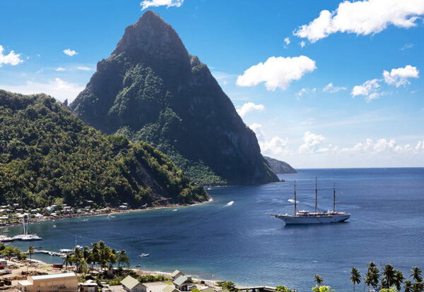 A shot of a ship coming into the harbour at Soufriere in  southern St. Lucia. Gros Piton in the background.